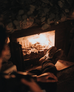 Picture of a man enjoying a fire following a thorough gas fireplace cleaning.